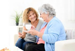 Elderly lady having tea with woman